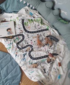 pokój dziecka i łóżko dla dziecka na którym leży otulacz bambusowy w zwierzęta, książka A królik słuchał, mata liść