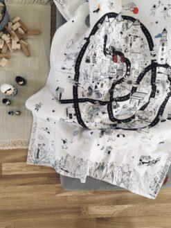 czarno biała narzuta na łóżko i pokój dziecięcy z matrioszkami i drewnianymi klockami, spanie na materacu montessori metoda
