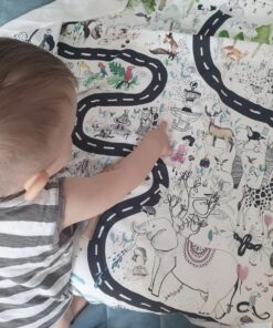 mały chłopiec pokazuje zwierzę na macie edukacyjnej dla dzieci